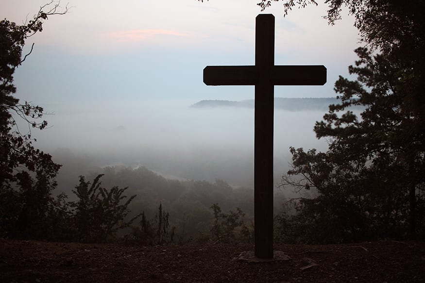 Cross overlooking cloudy valley