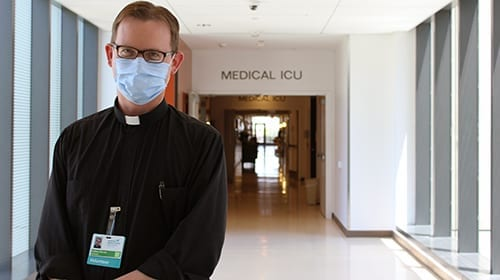 Father Kevin Dyer, SJ, provides pastoral comfort to patients at University Hospital in New Orleans.