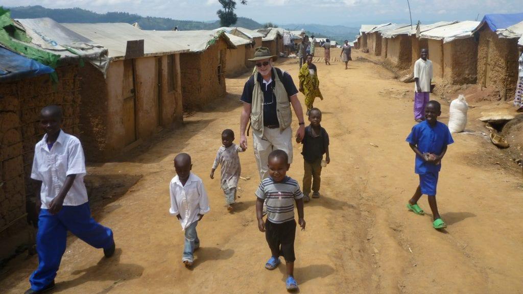 Father Gallagher walks with refugee children.