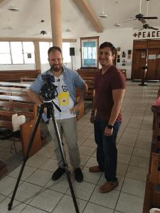 Father Zipple working with a parishioner on the parish's livestream capabilities.