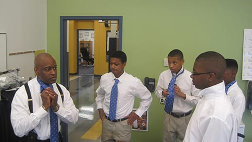 Dr. Clark teaches students how to tie a tie.